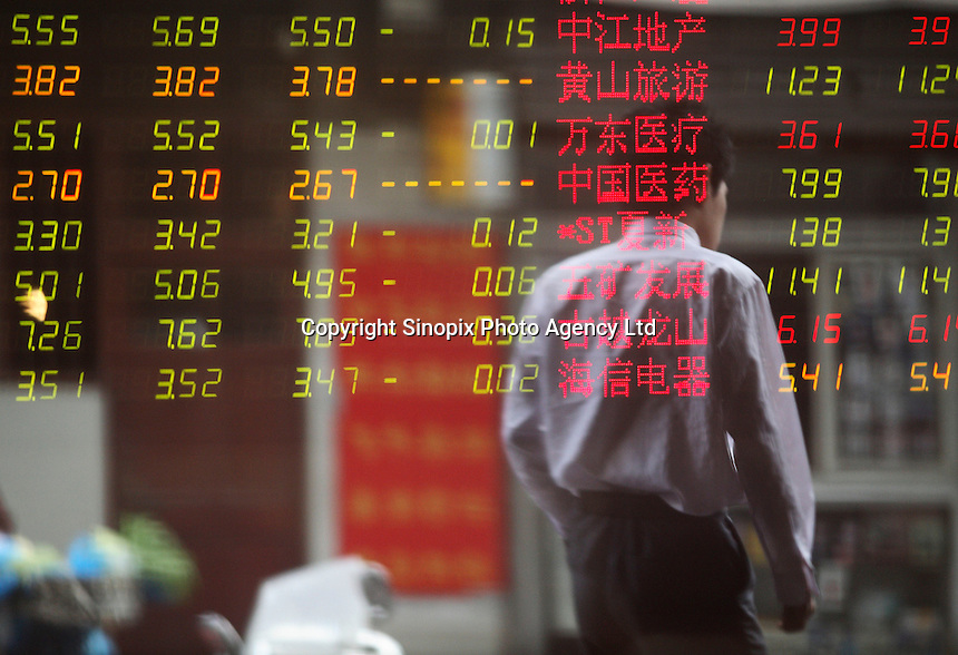 Images of pedestrians is reflected on a glass panel at a securities exchange house in Shanghai, China..20 Oct 2008