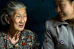 Sosorbaram, an 82-year-old woman in Khanuul, a ger (tent) district of Ulan Batur, talks to Red Cross Volunteer, Yunbat.<br /> <br /> The Red Cross has helped Sosorbaram get state assistance for her own ger and also a state allowance for firewood. Sosorbaram's husband and daughter are dead, so Red Cross volunteers' regular visits also provide her with much needed companionship.