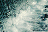 close-up of waterfall edge dropping to level ground in fountain. water, motion.