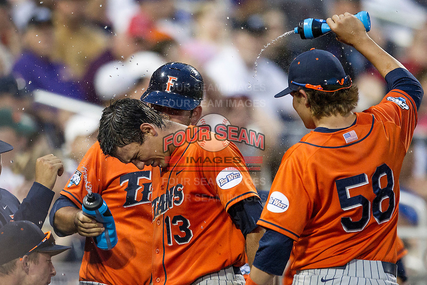 Cal State Fullerton Titans shortstop Timmy Richards (13) is showered with water after scoring during the NCAA College baseball World Series against the Vanderbilt Commodores on June 14, 2015 at TD Ameritrade Park in Omaha, Nebraska. The Titans were leading 3-0 in the bottom of the sixth inning when the game was suspended by rain. (Andrew Woolley/Four Seam Images)