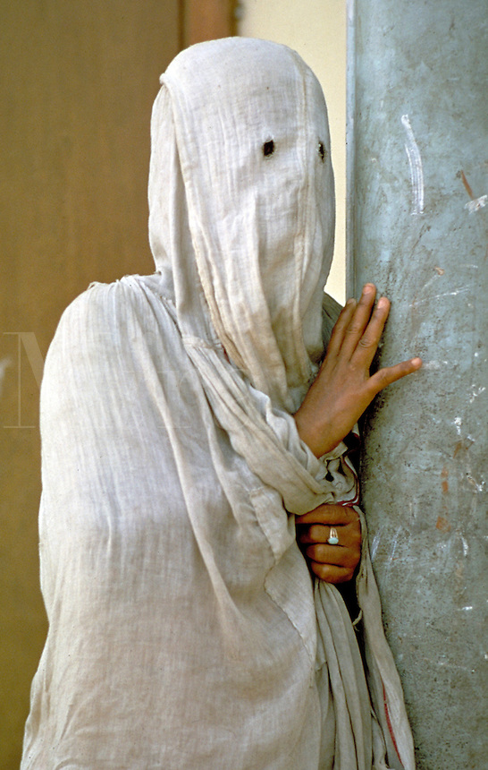 A Muslim woman wears a while burkah in Purdah in Pakistan. Although the women may wear more or less fancy burkahs (the cloth covering the body), the principle is the same; no one except their husband and female members of their immediate family may s ee t