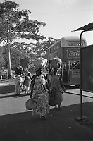 """Five native women in colorful clothing with a child on a sidewalk - Kampala, Uganda , NOV or DEC 1961.<br /> <br />  On the right a bus with advertisements for """"Drink Coca-Cola"""" and """"Dunlop"""