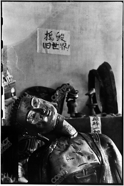 """In the aftermath of the destruction of Jile Temple, a sign posted on the wall reads, """"smash the old world"""", and damaged statues are desecrated with paper dunce caps. Harbin, 24 August 1966"""