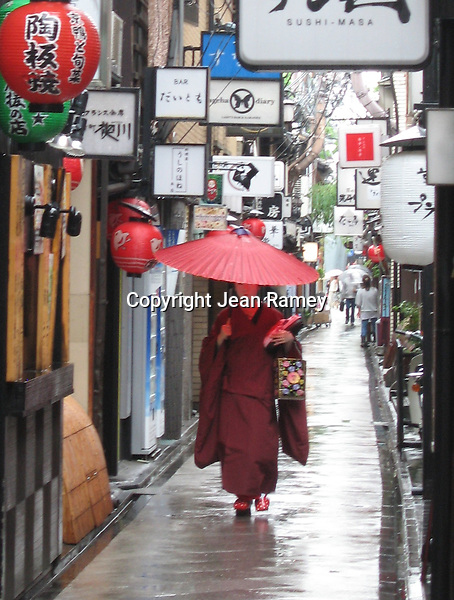 Geisha in Pontocho. A Geisha walks through Pontocho with a red Japanese umbrella