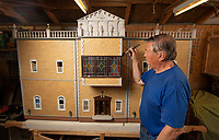 BNPS.co.uk (01202) 558833<br /> Pic: ZacharyCulpin/BNPS<br /> <br /> Len Martin, with his mansion<br /> <br /> A model maker who spent 25 years building a stunning miniature Georgian mansion has put it up for sale for £8,750.<br /> <br /> Len Martin spared no expense or time in creating the incredibly ornate model home that includes Swarovski chandeliers, gold furniture and artwork from Egyptian King Farouk's artist.<br /> <br /> The 42ins tall property also boasts a sweeping driveway, 16 statues, 138 balustrades, marble floors, stone cherubs on the ceilings and more tiny oil paintings crafted by real artists.