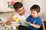 Three year old boy playing with toy vehicles and father, talking