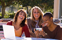 Mixed ethnic women friends relaxing at home laughing with cell phone camera IPhone in sunshine with computer