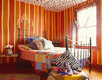 The vertical stripes which decorate the walls of the master bedroom were all painted by hand, the ceiling is painted with strawberries and the iron-framed bed is covered in textiles