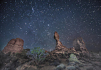 The night sky comes alive beyond Balanced Rock at Arches National Park, Utah