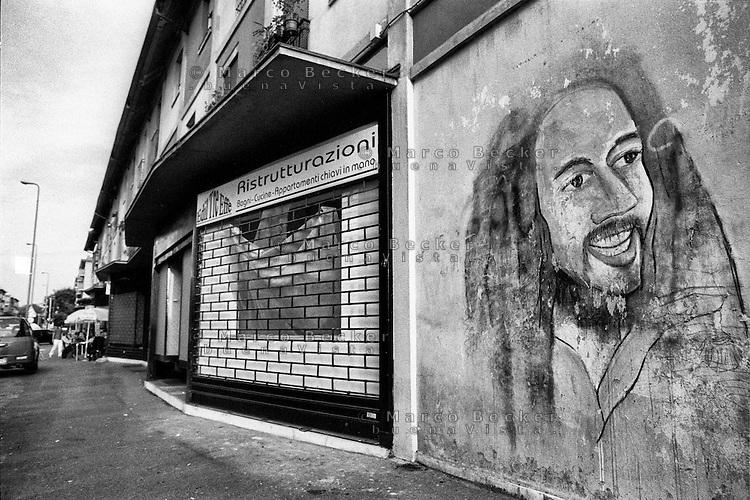 Milano, quartiere Quarto Oggiaro, periferia nord. Bob Marley dipinto su un muro e una impresa di ristrutturazioni con la serranda abbassata --- Milan, Quarto Oggiaro district, north periphery. Bob Marley painted on a wall and a restorations firm with its shutter closed