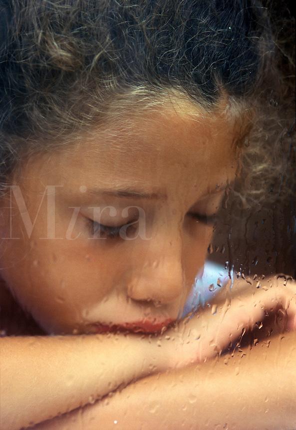 Sad girl by a rain streaked window.