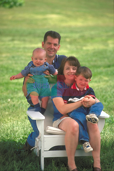 portrait of smiling family sitting in adirondack chair in park