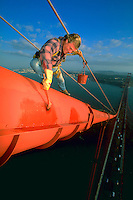 A bridge painter working with red paint and a brush high above San Francisco Bay on the Golden Gate Bridge in San Francisco, California.<br />