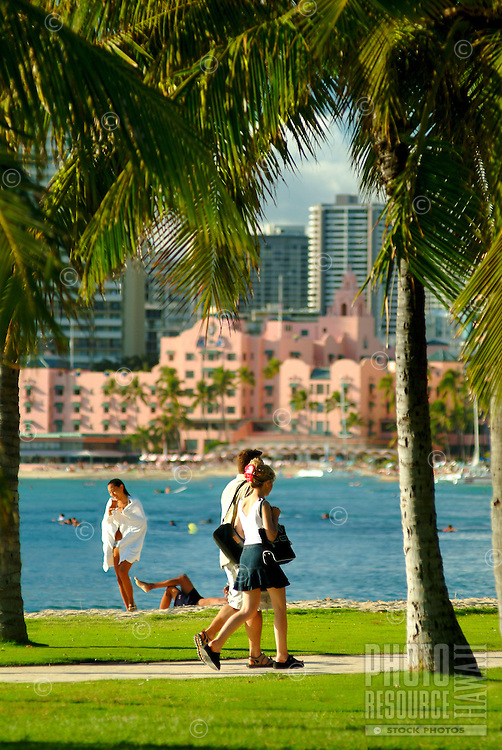 "A couple strolls along a palm tree lined path off  Waikiki Beach with the blue ocean and the Royal Hawaiian Hotel, or """"pink palace"""" in the background."