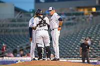 Northwest Arkansas Naturals pitching coach Doug Henry (19) (right) meets at the mound with pitcher Gerson Garabito (15) and catcher Meibrys Viloria (22) on May 16, 2019, at Arvest Ballpark in Springdale, Arkansas. (Jason Ivester/Four Seam Images)
