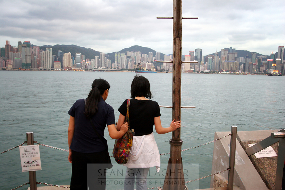 CHINA. Hong Kong. Two women look out onto Hong Kong Bay. Officially the Hong Kong Special Administrative Region, it is a territory located on China's south coast on the Pearl River Delta. It has a population of 6.9 million people, and is one of the most densely populated areas in the world. 2008