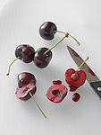 Sliced and whole bing cherries on a cutting board, with paring knife