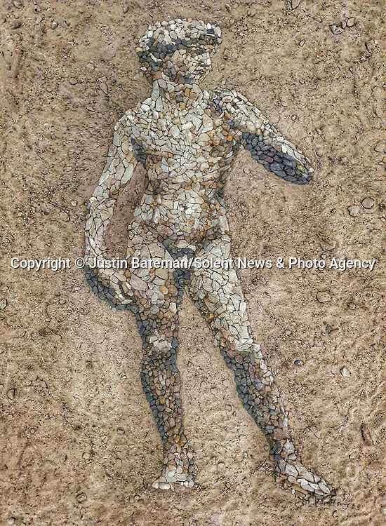 Pictured: Justin Bateman's version of Michelangelo's David made from pebbles<br /> <br /> A British artist stuck in Thailand has spent his time constructing masterpieces from pebbles for locals to enjoy.  Justin Bateman had only planned on staying in Chiang Mai for a week - but has remained there now for nearly ten months after the pandemic struck. <br /> <br /> His pebble portraits include The Queen, Spanish painter Pablo Picasso, Michelangelo's David and a local farmer - who was bemused by his portrait.   Mr Bateman, from Portsmouth, Hants, was staying in Bali when he travelled to Chiang Mai, in Thailand, to visit some friends.   SEE OUR COPY FOR DETAILS.<br /> <br /> Please byline: Justin Bateman/Solent News<br /> <br /> © Justin Bateman/Solent News & Photo Agency<br /> UK +44 (0) 2380 458800