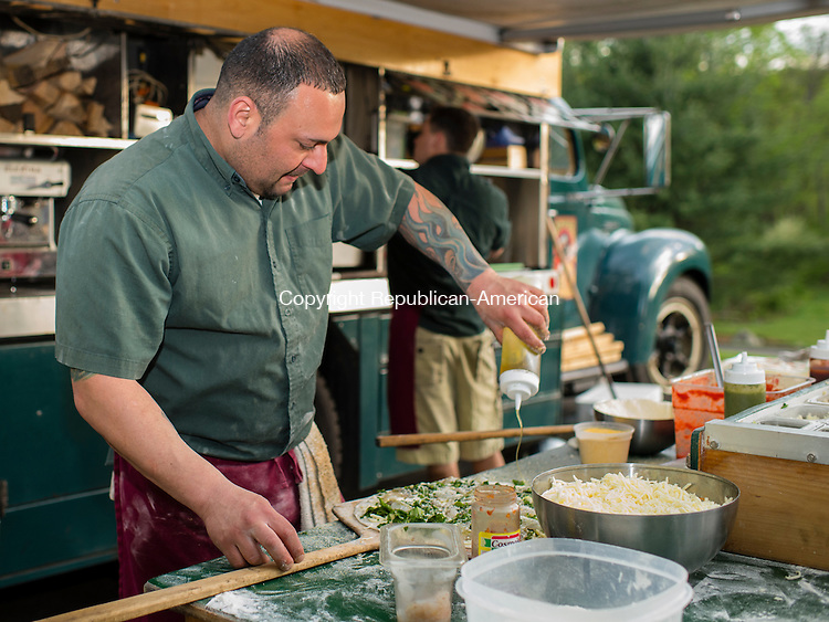 WATERTOWN, CT- 19 May 2016-051916EC10-  Joe Elcuri, with the Big Green Pizza Truck out of New Haven, puts toppings on a pizza ready for the oven during the Greater Waterbury Campership Fund's annual fundraiser Thursday night. The event was held at the Greater Waterbury YMCA's Camp Mataucha in Watertown. All money raised goes directly to the cost of sending children to camp. Erin Covey Republican-American