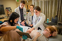 Physician assistant student and ultrasound technician Mailyn Williams teaches Alaska WWAMI Program medical students Bonnie Snyder, Hope Spargo, and Evan Gross to use a portable ultrasound on classmate Zane Davis as their class learns the basics of ultrasound in UAA's Health Sciences Building.