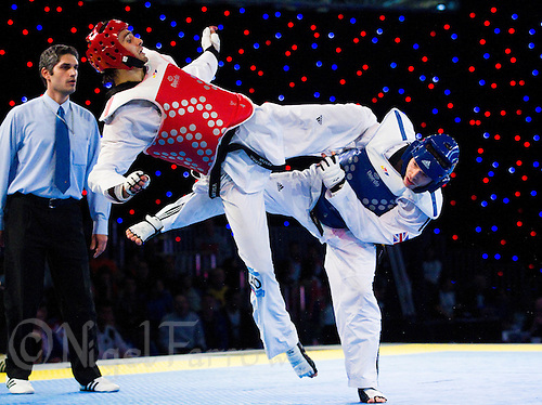 05 MAY 2012 - MANCHESTER, GBR - Aaron Cook (GBR) of Great Britain (right in blue) tries to evade a kick from Ramin Azizov (AZE) (left in red) of Azerbaijan during the men's 2012 European Taekwondo Championships -80kg final at Sportcity in Manchester, Great Britain (PHOTO (C) 2012 NIGEL FARROW)