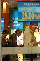People take money from service tills (ATM) at a branch of Standard Chartered Bank in Hong Kong..