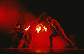 Natal, Brazil. Dancers at a folklore show made up as Indians in red light with flaming torches.