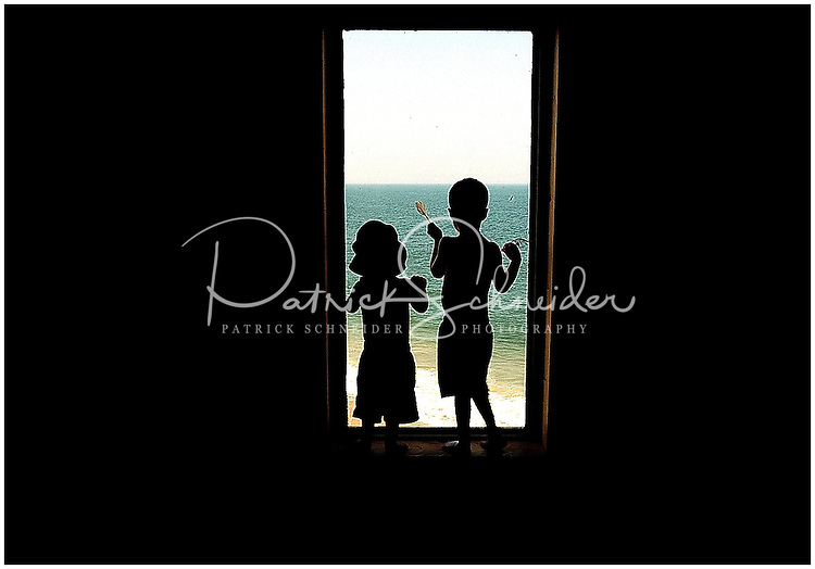 Two boys, silhouetted in a hotel window, look out at the ocean in the North Carolina Outer Banks. Model released.