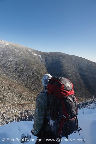 Snow covered hiker takes in the view of the Pemigewasset Wilderness from a view point along the Frost Trail in the New Hampshire White Mountains during the winter months. Southwest Twin Mountain is in view.