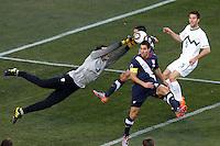 Samir Handanovic goalkeeper of Slovenia (left) dives to save the ball under pressure from Carlos Bocanegra of USA