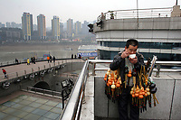 CHINA. Sichuan Province. Chongqing. A man selling traditional Chinese flutes near The Yangtze River which is at its lowest level in 150 years as a result of a country-wide drought. Chongqing is a city of over 3,000,000 people, famed for being the capital of China between 1938 and 1946 during World War II. It is situated on the banks of the Yangtze river, China's longest river and the third longest in the world. Originating in Tibet, the river flows for 3,964 miles (6,380km) through central China into the East China Sea at Shanghai.  2008