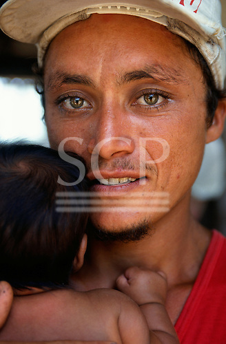 Para State, Brazil. Young caboclo father with green eyes and a straggly beard holding his baby.