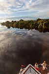 Navigation sur le Rio Negro au nord de Manaus sur le bateau de croisière La Jangada<br /> <br /> <br /> Les nuages et le bateau se reflètent dans les eaux noires du Rio Negro