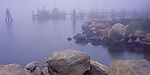 Mystic,  CT: Morning Fog envelopes a fishing dock and boulders on the shore of Mystic Harbor in the village of Noank