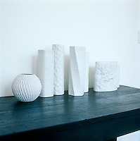 In the living room a collection of contemporary white porcelain vases is offset by the dark wooden surface of the table on which they are displayed