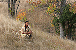 A native american indian boy squating in the long dried grass during a Fall season in South Dakota