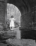 A Little Girl in Her Sunday School Dress looking through a tunnel with a river