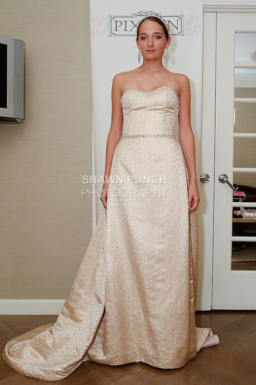 Model poses in an Elinor wedding gown from the Pixton Couture Bridal Spring 2014 collection, by Kimberly Pixton Millar, during New York Bridal Market Week Spring 2014.