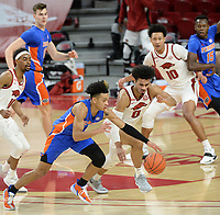 Florida guard Tre Mann (left) and Arkansas guard Justin Smith (0) reach Tuesday, Feb. 16, 2021, for a loose ball during the first half of play in Bud Walton Arena. Visit nwaonline.com/210217Daily/ for today's photo gallery. <br /> (NWA Democrat-Gazette/Andy Shupe)
