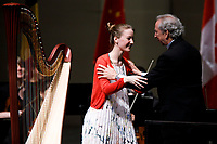 Mathilde Wauters of Belgium embraces Indiana University Summer Philharmonic Orchestra conductor Arthur Fagen after her performance during the Stage IV concert at the 11th USA International Harp Competition at Indiana University in Bloomington, Indiana on Saturday, July 13, 2019. (Photo by James Brosher)