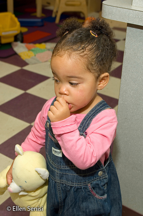 MR / Schenectady, NY.Schenectady Day Nursery / private non-profit daycare center / Toddler class.Toddler (girl, 1, African-American / Caucasian), with tears in her eyes, sucking her thumb, holds a stuffed animal..MR: Far3.© Ellen B. Senisi