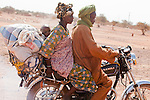 Curious mixes of ancient tradition and modernity co-mingle throughout Africa.  In the town of Djibo in northern Burkina Faso, a Fulani family zips by on a motorcycle.  The driver's wife carries a toddler strapped to her back in a centuries-old African fashion.