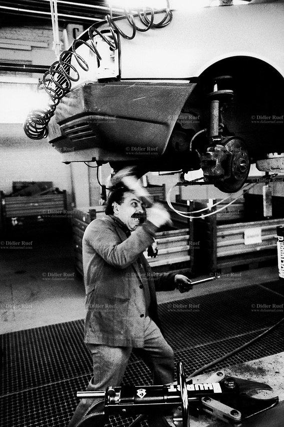 Italy. Torino Region. Torino. Mirafiori is the main FIAT factory. FIAT Auto Recycling Program (F.A.R.E.). Dismantling station for old derelict motor vehicles. A worker with a hammer tries to loosen a fixed screw bolt. © 1993 Didier Ruef