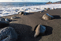 oamy waves flowing onto rocks and black sand at Kehena Beach, Pahoa, Big Island.