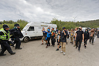 Pictured: Revellers follow on as police officers move away. Monday 31 August 2020<br /> Re: Around 70 South Wales Police officers executed a dispersal order at the site of an illegal rave party, where they confiscated sound gear used by the organisers in woods near the village of Banwen, in south Wales, UK.