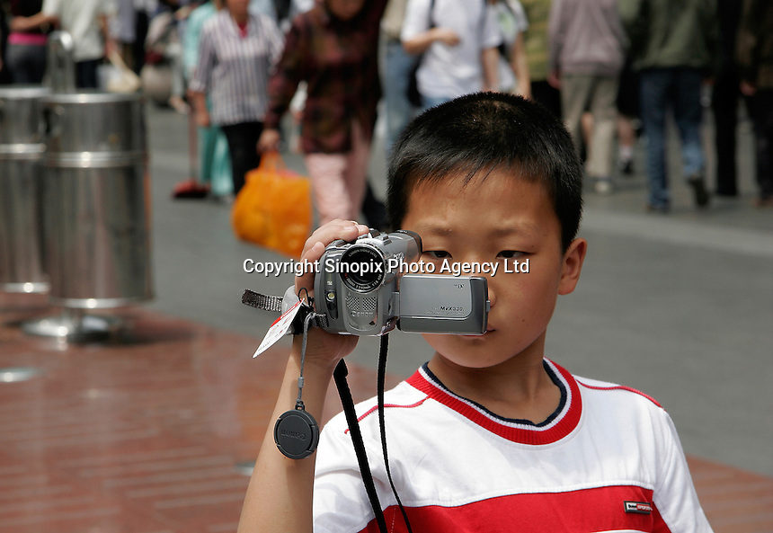 A child uses a just purchased video camera in Shanghai, China..04 May 2005
