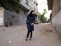 """Amira Al-Qerem (16) walks, with some difficulty from the injury to her right leg, in her old neighbourhood in Gaza City on October 27 2010. Amira was missing and presumed dead after she was injured by one of the same explosions that killed her father, brother and sister during the last days of the Israeli invasion of Gaza in 2009. She was found three days later, after her family thought they had buried her remains with those of the other three. She is one of the main subjects of the controversial documentary film """"Tears of Gaza"""" by director Vibeke Løkkeberg."""