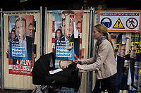 """France. Ile de France. Paris. Partially torn campaign posters of French presidential election candidate Emmanuel Macron for the centrist party """"En Marche"""". A mother is pushing her baby stroller near a construction site. 22.04.17 © 2017 Didier Ruef"""