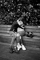 Italy. Lombardy Region. Porlezza. A young loving couple sits on a wooden bench. The man and the woman kiss with passion.10.10.2020 © 2020 Didier Ruef