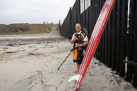 """Tom Jones poses for photographers in front of the US Mexico border at Border Field State Park, the south-western most corner of the contiguous United States, Fiday, November 9 2007.  Jones became the first person to paddle the entire 1250-mile coast of the California on a paddleboard when his three and a half month long journey ended at the border fence in southern San Diego.   The expedition, called """"California Paddle 2007? was designed to draw attention to the problem of plastic pollution in the world?s oceans and its detrimental effect on marine life.  (Photo Ronan Gray)"""